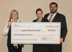 RLS attorneys Sarah Burdick and Jonathan Murphy handing Dee Dee Lundquist a check for attorneys' fees awarded against the City of Oakland in the Mausz arbitration.